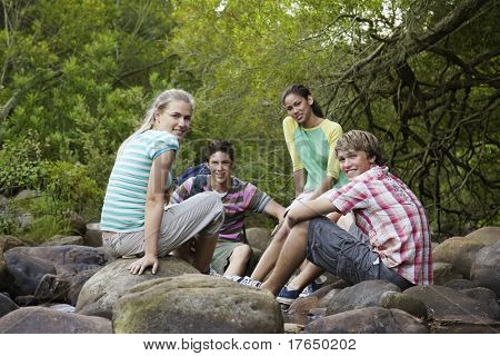 Portrait of four teenagers (16-17 years) sitting on stones by river, smiling