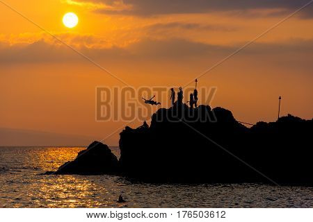 Silhouette of Diver Leaping off Rock and into the Water around Sunset in Maui Hawaii