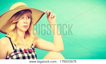 Portrait of attractive lovely blonde young woman wearing charming checked dress and sun hat. Summeral fashion concept. Studio shot on light blue background