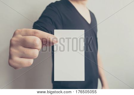 Close up hand of casual man black shirt holding blank business card on concrete wall background