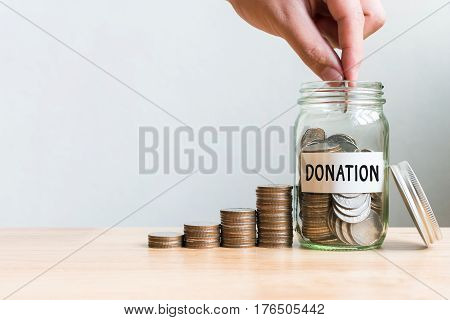 Hand putting coin in jar labeled donation with money stack. Concept business finance and investment