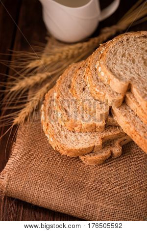 sliced whole wheat bread on wooden table dark background