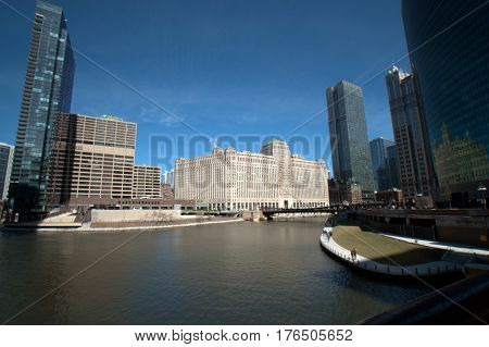 Wolf Point and Merchandise under a clear blue sky and a Chicago River dyed green for Saint Patrick's Day