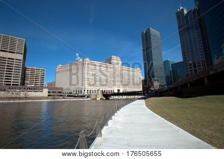 Merchandise Mart beside a Green Chicago River and the rive walk under a clear blue sky