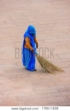 Woman sweeping Jaleb Chowk - main courtyard of Amber Fort Rajasthan India. Amber Fort is the main tourist attraction in the Jaipur area. poster
