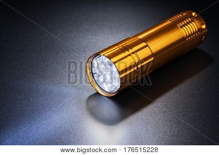 Luminous flashlight on dark surface. light, led,