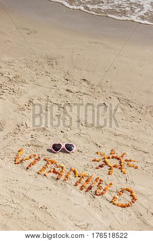Sunglasses inscription vitamin D and shape of sun made of amber stones on sand at beach concept of vacation time and prevention of vitamin D deficiency
