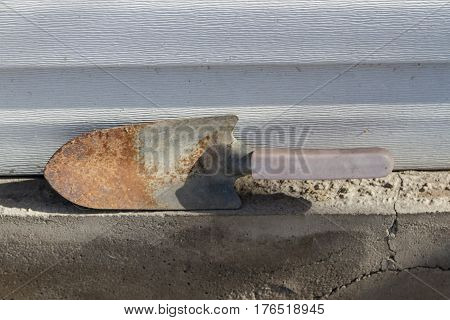 old rusty garden trowel against the wall of siding