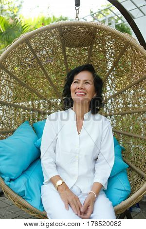 Happy senior Vietnamese woman sitting in cocoon chair