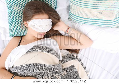 Close-up of beautiful young woman sleeping in bed with eye mask. Indoors.