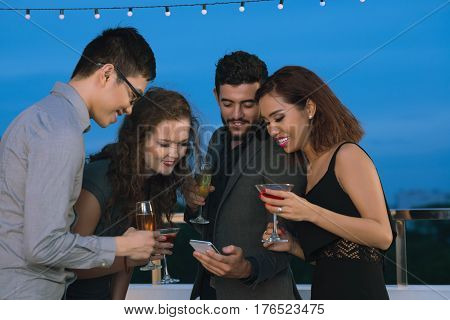 Young man showing something interesting on smartphone to friends at party