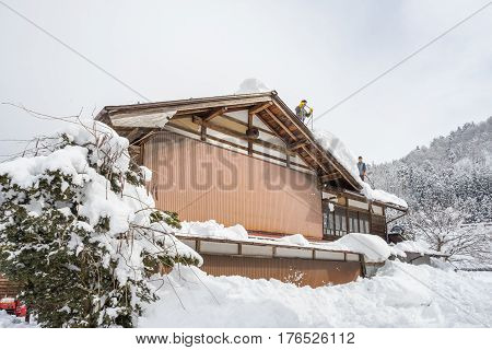 Shirakawa, Japan - 14 FEB 2017: Worker cleaning roof house from snow at Shirakawa-go village, Japan.Winter in Shirakawa-go Japan