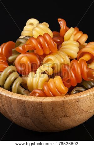 Spiral pasta trottole tricolore isolated in wooden bowl on black background close up