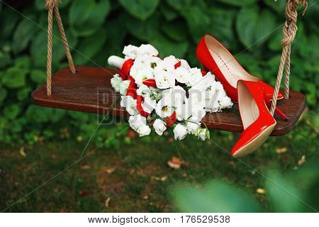 Attributes runaway bride. Wedding bouquet of white roses and red ribbons and red patent leather high-heeled shoes