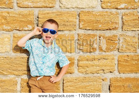 Little Boy Wearing Blue Mirror Sunglasses Against The Yellow Brick Wall Outdoors