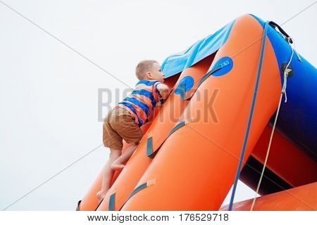 Little boy playing on an inflatable playground on the beach on a summer day.