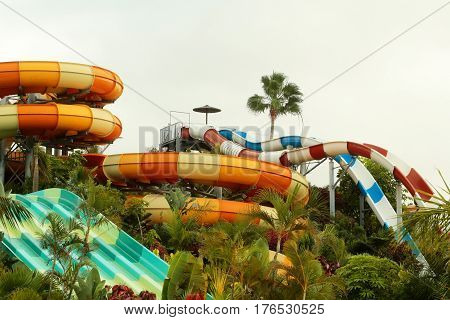 Beautiful water or aqua park with colorful waterslides in resort town with green tropic garden outdoors on summer day on cloudy blue sky background