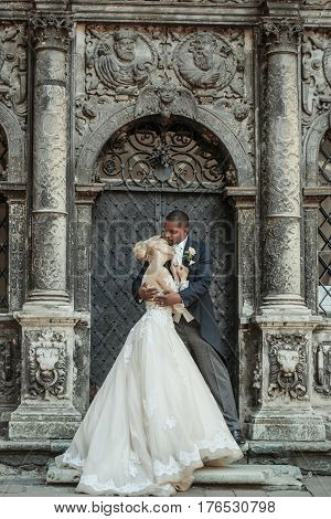 Handsome man or african American groom hugging pretty girl or cute bride with beautiful blond hair in white sexy wedding dress outdoors at ancient building door on grey background