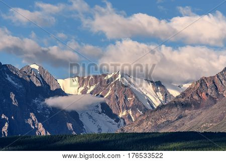Scenic view with snow-capped mountain peaks in beautiful fluffy clouds and green forests on the background of the blue sky