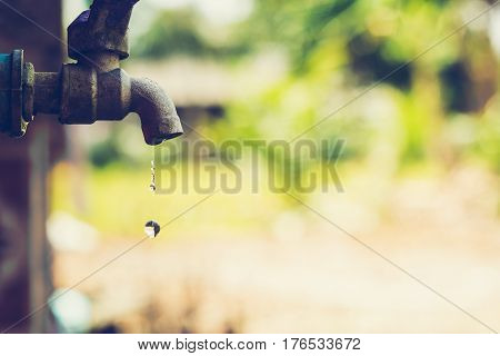 water drop from tap with blur nature background,Leaking water