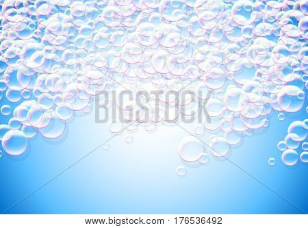 Soap bubbles blue background with rainbow colored airy foam