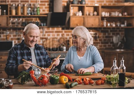 Portrait Of Smiling Senior Couple Making Salad Together In Kitchen