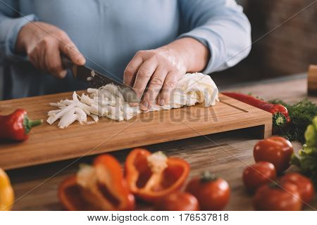 partial view of senior woman chopping onion for salad