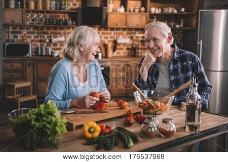 Happy Senior Couple Cooking Together And Smiling Each Other
