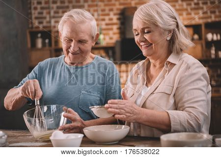 Smiling Senior Couple Cooking Together At Kitchen Table