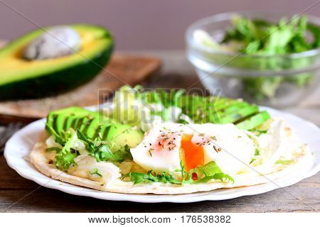 Healthy breakfast with a poached egg, avocado slices, chinese cabbage, lettuce, tortilla, sauce and spices. Simple avocado and poached egg tortilla on a plate and on old wooden background. Closeup