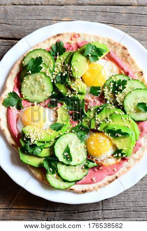 Vegetarian tortilla on a plate and on a wooden table. Easy and quick tortilla piled high with fried quail eggs, avocado, cucumbers, sesame seeds and parsley and lathered with beetroot hummus. Top view