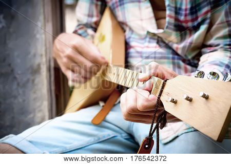 Handsome Hands Of Man Playing Music With Balalaika At Grey Wall Background.