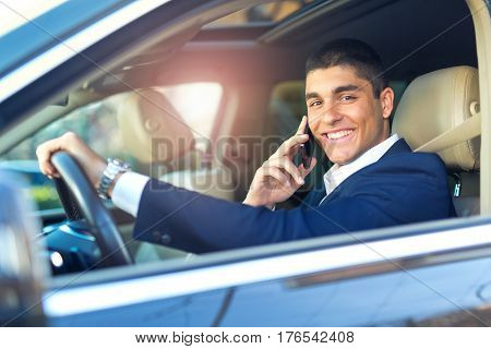 Businessman talk in car. Confident businessman talking on the mobile phone and looking away while driving his car.