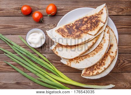 Quesadilla with meat and onion , tomato on wooden table
