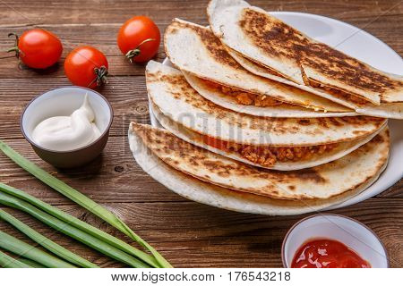 Quesadilla with chicken, green onion, tomatoes, dressing on wooden table
