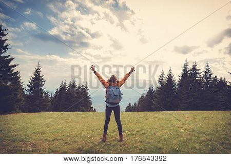 Girl enjoying on the field with arms wide open.