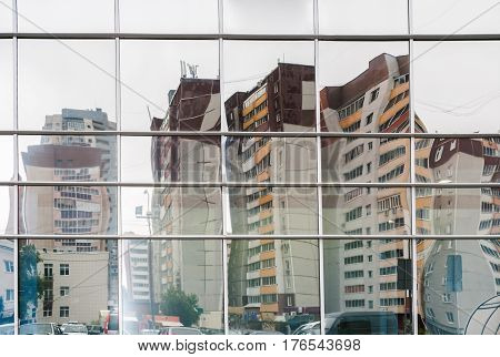 Distorted reflection of  several multi-storey residential buildings in mirror surface of facing of Mall opposite houses.