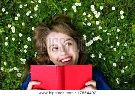 Frau auf Gras liegend mit Buch