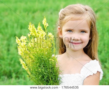 Adorable smiling little girl with flowers on the meadow in summer day