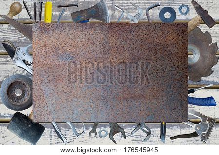 A lot of old shabby scratched tool on a wooden background. In the middle there is a place for an inscription on a rusty iron background. flat lay.