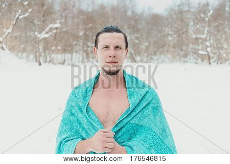 Young man standing with towel after swimming and hardening in winter to promote health looking at camera
