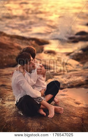 By the sea at sunset sitting on stones the father carefully embraces his son