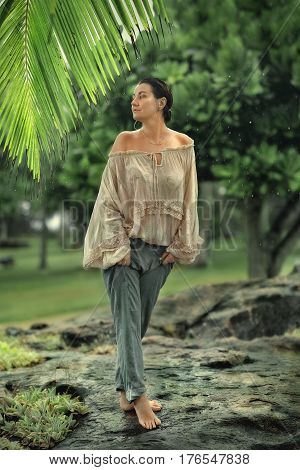 In the rain under the palm tree is a barefoot woman in trousers with wet hair