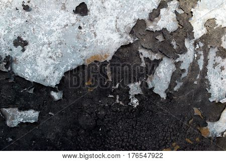 The tar texture is peeling off the metal surface. Rust spots. Horizontal background.