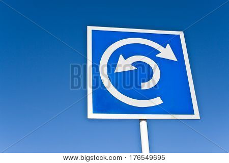 Roundabout traffic sign over a blue sky