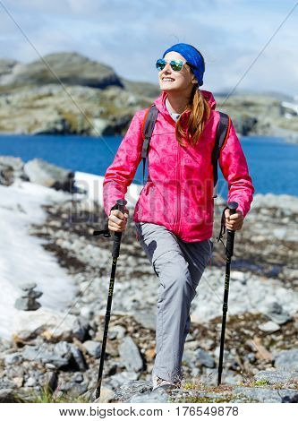 Happy hiking girl with trekking sticks in the mountains. Norway