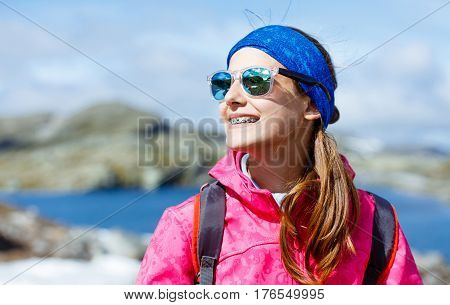 Portrait of happy hiking girl with trekking sticks in the mountains. Norway