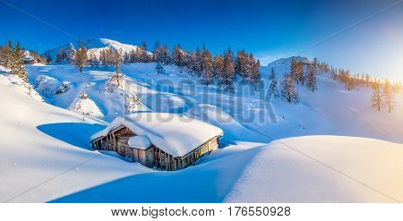 Panoramic view of beautiful winter mountain landscape with snow capped mountain cabin in the Alps in golden evening light at sunset