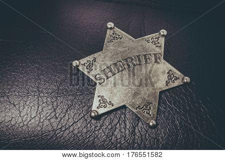 Sheriff badge on black leather texture background. Macro shot.