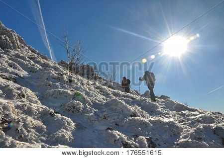 Couple of mountaineers hiking on snowy mountain into the sun